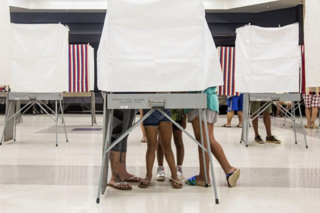 A family squeezes together inside of a small voting booth at Kapolei High School in Kapolei, Hawaii., Saturday, Aug. 11, 2018. The winners of most of the Democratic Party's primary races in Hawaii this weekend will be the favorites to win the general election in November. The most hotly contested …