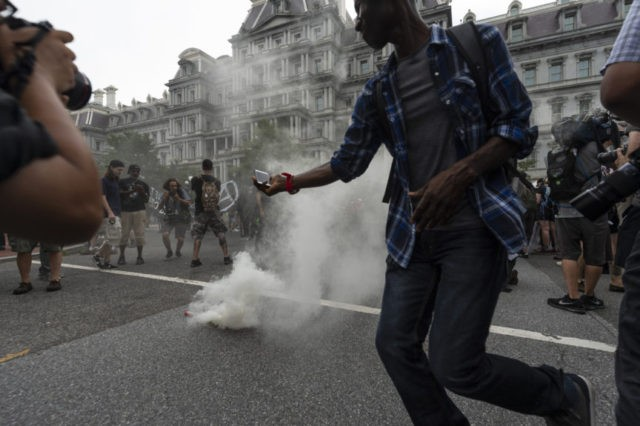 """Journalists photograph a type of smoke grenade placed by Antifa-activists in the middle of 17th street during the """"Unite the Right 2"""" rally in Washington, Sunday, Aug. 12, 2018. (Craig Hudson/Charleston Gazette-Mail via AP)"""