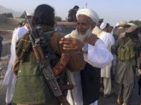 In this June 16, 2018 file photo, Taliban fighters gather with residents to celebrate a three-day cease fire marking the Islamic holiday of Eid al-Fitr, in Nangarhar province, east of Kabul, Afghanistan. On Sunday, Aug. 19, 2018, Afghan President Ashraf Ghani announced a conditional cease-fire with Taliban insurgents for the …