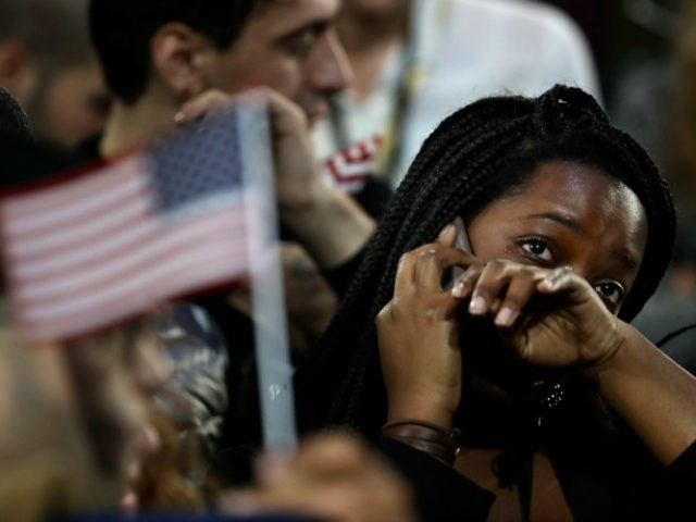 FILE - In this Nov. 8, 2016 file photo, a woman weeps as election results are reported during Democratic presidential nominee Hillary Clinton's election night rally in the Jacob Javits Center glass enclosed lobby in New York. As Donald Trump approaches his inauguration as president, young Americans have a deeply …