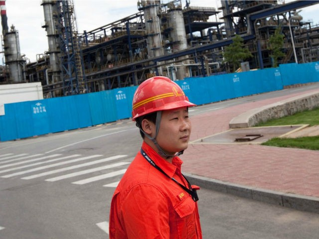 A worker at the China Petroleum & Chemical Corp. Yanshan refinery escorts journalists in Beijing