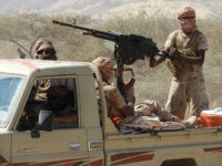 Yemeni fighters loyal to the government backed by the Saudi-led coalition fighting in the country ride in the back of a pickup truck with mounted heavy machine gun while closing in on a suspected location of an Al-Qaeda in the Arabian Peninsula (AQAP) leader during their the offensive in the …