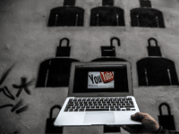 A laptop computer showing Youtube's logo on its screen is held in front of graffiti on March 27, 2014 in Istanbul. Turkey on March 27 banned video-sharing website YouTube, a week after blocking access to Twitter, after both were used to spread audio recordings implicating the prime minister in corruption, …