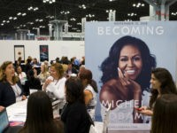 A poster for former first lady Michelle Obama's memoir, Becoming, is displayed in the Penguin Random House exhibit, Thursday, May 31, 2018 at Book Expo in New York. the book will be available in November. (AP Photo/Mark Lennihan)