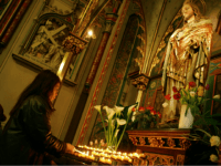 Worshippers light candles and pray next to a statue of Jesus in a Roman Catholic church in Amsterdam, Netherlands, Friday April 1, 2005. Pope John Paul II is in grave condition, the vatican said Friday, but it said he is lucid and spent the morning celebrating mass and receiving top …