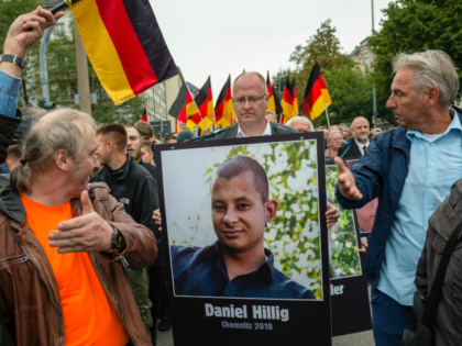People take part in a march of silence organized by the right-wing Alternative for Germany (AfD) political party and carry German flags and portraits of supposed victims of refugee violence on September 1, 2018 in Chemnitz, Germany. (Jens Schlueter/Getty Images)