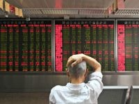 A man checks stock price movements at a securities company in Beijing on July 4, 2018.