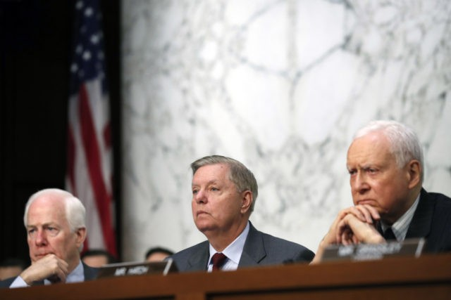 Sen. John Cornyn, R-Texas, left, and Sen. Orrin Hatch, R-Utah,, right, listen as Sen. Lindsey Graham, R-S.C., as President Donald Trump's Supreme Court nominee Brett Kavanaugh answers a question as he testifies before the Senate Judiciary Committee on Capitol Hill in Washington, Thursday, Sept. 6, 2018, for the third day …
