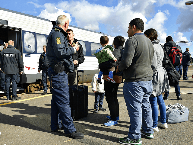 Refugees, mainly from Syria, speak with a Danish policeman after arriving in Rodby, southern Denmark, from Germany on September 7, 2015. Europe's migrant crisis has exposed sharp rifts in the 28-nation European Union, with Germany leading calls to take in many more people fleeing war and upheaval in the Middle …