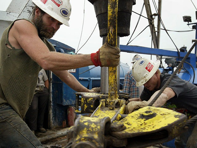 OKAWVILLE, IL - OCTOBER 9: Jerry McKinney (L) and Jeremy Beck work a drilling rig as they search for oil for Houston, Texas based Vintage Exploration in a corn field October 9, 2004 near Okawville, Illinois. High oil prices and low finding cost in the region which has relatively shallow …