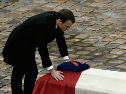 TOPSHOT - French President Emmanuel Macron places his hands on the flag-draped coffin of Lieutenant-Colonel Arnaud Beltrame after awarding him posthumously with the Legion of Honour during a national ceremony on March 28, 2018 at the Hotel des Invalides in Paris. France honours during a national ceremony on March 28 …