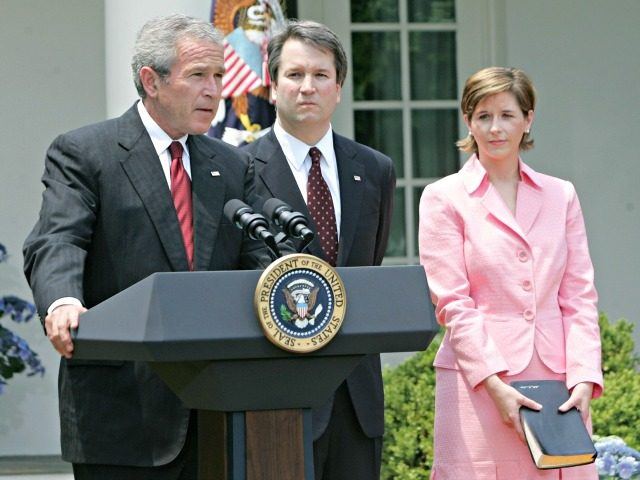 President Bush, speaks in the Rose Garden of the White House before the swearing-in of Brett Kavanaugh, center, as Judge for the U.S. Court of Appeals for the District of Columbia Thursday, June 1, 2006 in Washington. Holding the Bible is Kavanaugh's wife Ashely Kavanaugh.
