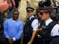 Alleged renegade UBS trader Kweku Adoboli, second from left, walks to be taken away in a security van flanked by police officers after appearing at the City of London Magistrates Court in London, Friday, Sept. 16, 2011. The alleged renegade trader accused of losing Swiss bank UBS about $2 billion …