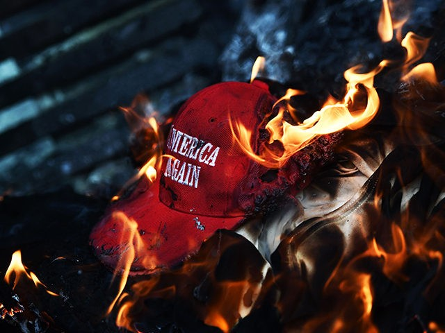 Anti-Trump demonstrator set a 'Make America Great Again' hat on fire in Washington, DC, on January 20, 2017. Masked, black-clad protesters carrying anarchist flags smashed windows and scuffled with riot police Friday in downtown Washington, blocks away from the route of the parade in honor of newly sworn-in President Donald …