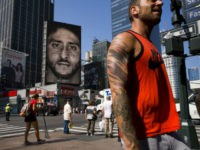 CORRECTS DATE- People walk by a Nike advertisement featuring Colin Kaepernick on display, Thursday, Sept. 6, 2018 in New York. Nike this week unveiled the deal with the former San Francisco 49ers quarterback, who's known for starting protests among NFL players over police brutality and racial inequality. (AP Photo/Mark Lennihan)