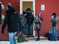 Refugees are welcomed upon arrival at the Norwegian border crossing station at Storskog after crossing the border from Russia on November 12, 2015 near Kirkenes. An increasingly popular route for migrants across Russia and into Norway has Oslo angered and worried as winter approaches, while commentators suspect Moscow is deliberately …