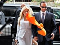 "An orange shirt saying ""inmate"" is thrown by a protester at former Donald Trump presidential campaign foreign policy adviser George Papadopoulos, right, who triggered the Russia investigation, and who pleaded guilty to one count of making false statements to the FBI, as he holds hands with his wife Simona Mangiante …"