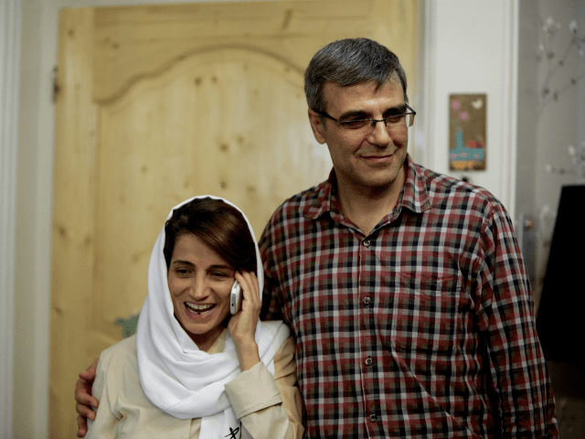 Iranian lawyer Nasrin Sotoudeh (L) speaks on the phone next to her husband Reza Khandan as they pose for a photo at their house in Tehran on September 18, 2013, after she was freed following three years in prison. Sotoudeh told AFP she was in 'good' physical and psychological condition, …
