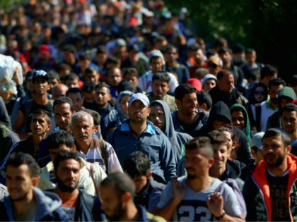 HEGYESHALOM, HUNGARY - SEPTEMBER 22: Hundreds of migrants who arrived on the second train today at Hegyeshalom on the Hungarian and Austrian border, walk the four kilometres into Austria on September 22, 2015 in Hegyeshalom, Hungary. Thousands of migrants have arrived in Austria over the weekend with more en-route from …