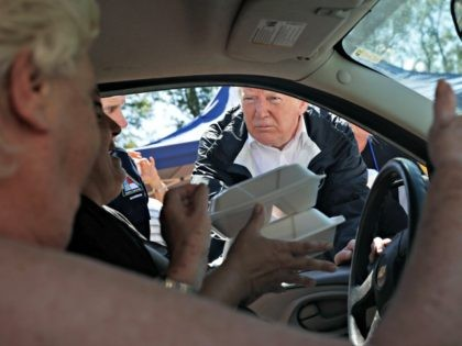 President Donald Trump and North Carolina Gov. Roy Cooper, left, hand out food at Temple Baptist Church, where food and other supplies are being distributed during Hurricane Florence recovery efforts, Wednesday, Sept. 19, 2018, in New Bern, N.C.