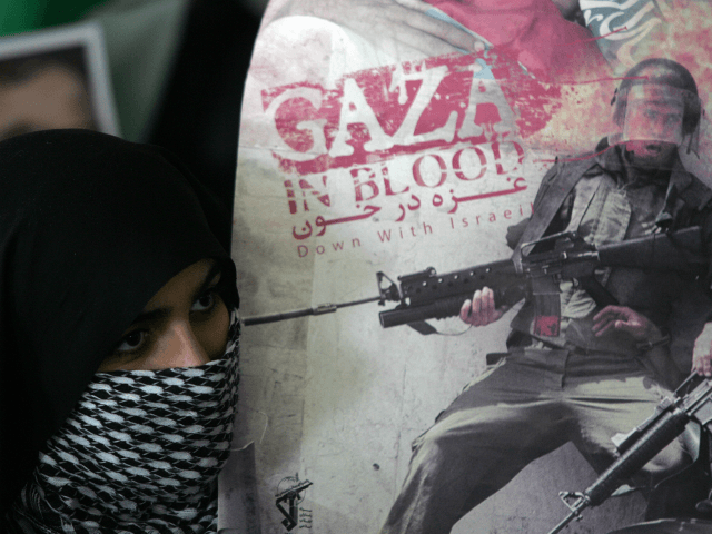 An Iranian student, covering her face with a Palestinian chequered keffiyeh, holds an anti-Israel poster during a demonstration held at Tehran University on January 20, 2009 to celebrate Hamas' 'victory' at the end of Israel's three-week offensive on the Gaza Strip in which more than 1,300 Palestinians were killed before …