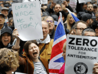 A woman holds up a placard declaring 'Corbyn made me a Tory' as she joins protesters gathering for a demonstration organised by the Campaign Against Anti-Semitism outside the head office of the British opposition Labour Party in central London on April 8, 2018. Labour leader Jeremy Corbyn has been under …