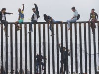 Migrant caravan demonstrators climb the US-Mexico border fence during a rally, on April 29, 2018, in San Ysidro, California. - The US has threatened to arrest around 100 Central American migrants if they try to sneak in from the US-Mexico border where they have gathered, prompting US President Donald Trump …