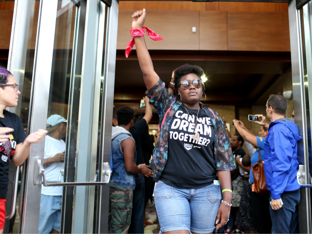 Protesters leave lthe lobby of the James Lawrence King Federal Justice Building where the U.S. Attorneys Office, Southern District of Florida, is located on August 14, 2014 in Miami, Florida. Eight who refused to leave were arrested. The protesters, which included members of the civil rights group Dream Defenders, say …