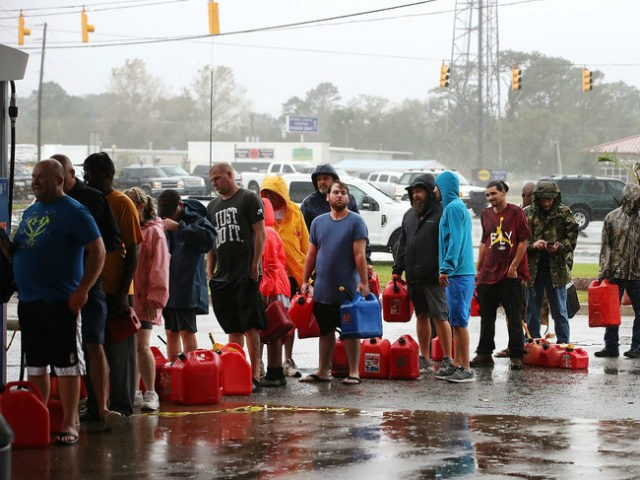WILMINGTON, NC - SEPTEMBER 15: People wait in line to fill up their gas cans at a gas station that was damaged when Hurricane Florence hit the area, on September 15, 2018 in Wilmington, North Carolina. Hurricane Florence made landfall in North Carolina as a Category 1 storm Friday and …
