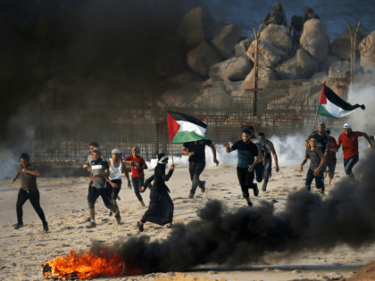 Palestinians run from tear gas smoke fired by Israeli forces (background) on the beach near the maritime border with Israel, in the northern Gaza Strip, during a protest calling for the lift of the Israeli blockade on the coastal Palestinian enclave, on September 10, 2018. (Photo by SAID KHATIB / …