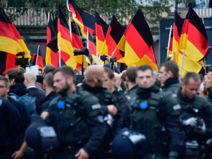 Supporters of the far-right Alternative for Germany (AfD) party wave German flags as they walk behind a barrage of riot police during a demonstration on September 1, 2018 in Chemnitz, eastern Germany. - The demonstration was organised in a reaction to a knife killing, allegedly by an Iraqi and a …