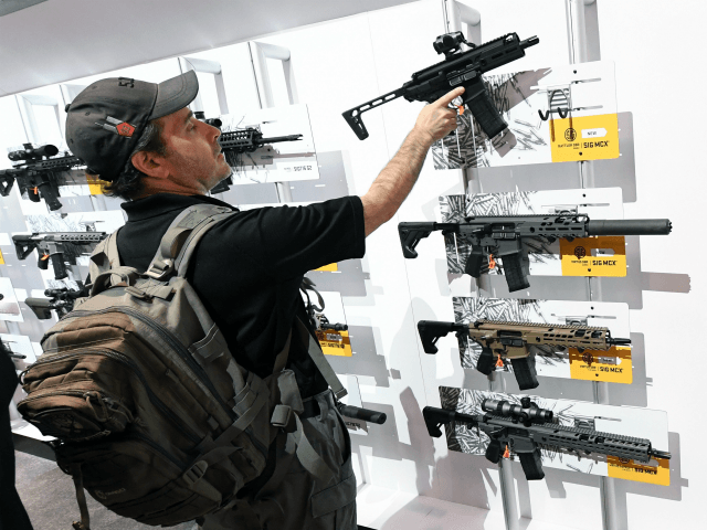 A convention attendee looks at rifles displayed at the Sig Sauer booth at the 2018 National Shooting Sports Foundation's Shooting, Hunting, Outdoor Trade (SHOT) Show at the Sands Expo and Convention Center on January 23, 2018 in Las Vegas, Nevada. The SHOT Show, the world's largest annual trade show for …