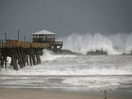 Waves crash around the Oceana Pier as the outer edges of Hurricane Florence being to affect the coast September 13, 2018 in Atlantic Beach, United States. Coastal cities in North Carolina, South Carolina and Virgnian are under evacuation orders as the Category 2 hurricane approaches the United States. (Photo by …