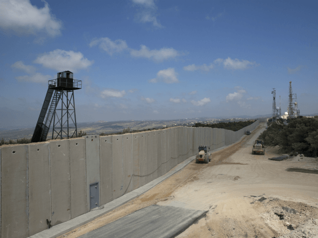 In this Wednesday, Sept. 5, 2018, photo, a bulldozer works near a wall at the Israel Lebanon border near Rosh Haniqra, northern Israel, Israel is building a massive wall along its northern border, saying the barrier is needed to protect civilians from Hezbollah attacks, but the project has raised tensions with Lebanon, which fears the fence will encroach on its territory. (AP Photo/Sebastian Scheiner)