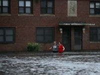 Residents wade through deep floodwater to retrieve belongings from the Trent Court public housing apartments after the Neuse River went over its banks during Hurricane Florence September 13, 2018 in New Bern, United States. Coastal cities in North Carolina, South Carolina and Virginia are under evacuation orders as the Category …