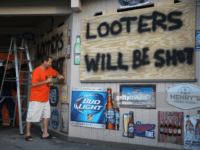 MYRTLE BEACH, SC - SEPTEMBER 12: Doug Lewis (L) and Chris Williams use plywood with the words 'Looters will be shot' to cover the windows of Knuckleheads bar as they try to protect the business ahead of the arrival of Hurricane Florence on September 12, 2018 in Myrtle Beach, United …