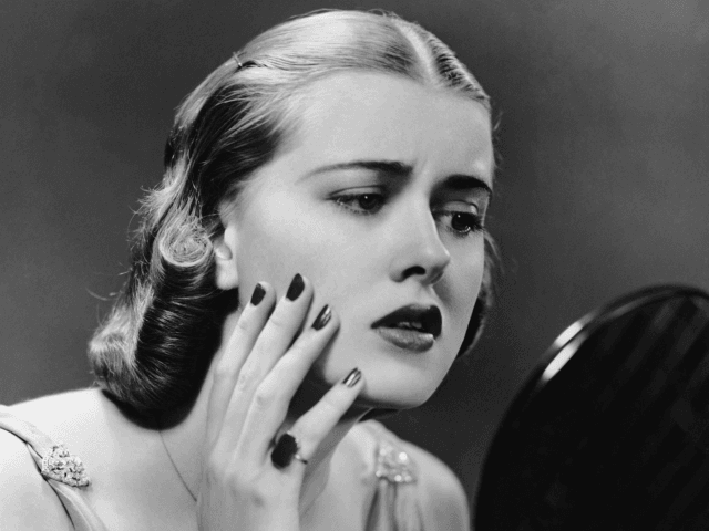 Portrait of upset woman looking in hand mirror. (Photo by George Marks/Retrofile/Getty Images)