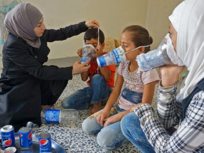 TOPSHOT - Um Majid (L) tries an improvised gas mask on familiy members in her home in Binnish in Syria's rebel-held northern Idlib province as part of preparations for any upcoming raids on September 12, 2018. - The Syrian regime and its Russian ally are threatening an offensive to retake …