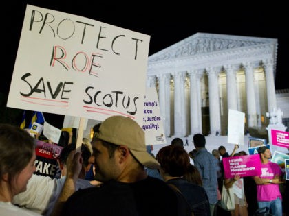FILE - In this July 9, 2018 file photo, demonstrators holds signs as they gather in front of the Supreme Court in Washington after President Donald Trump announced Judge Brett Kavanaugh as his Supreme Court nominee. Worried by the prospect of a reconfigured court, abortion-rights advocates are intensifying efforts to …