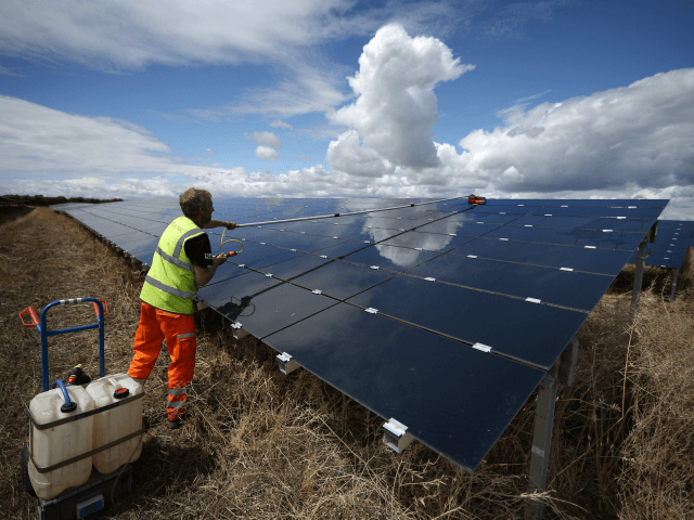 ABINGDON, ENGLAND - JULY 29: A workman cleans panels at Landmead solar farm on July 29, 2015 near Abingdon, England. The 46 megawatt capacity installation was the largest in the United Kingdom when it was completed in 2014. Operated by BELECTRIC UK it supplies around 45 million kWh (kilowatt hours) …