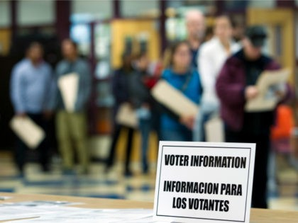 An information sign, also in Spanish, sits on the table as people wait to cast their ballots at the Takoma Park Middle School, in Takoma Park, Md., Tuesday, Nov. 8, 2016. ( AP Photo/Jose Luis Magana)