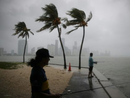 Walter Augier (L) and Jhon M. fish as rain and wind are whipped up by Tropical Storm Gordon on September 3, 2018 in Miami, Florida