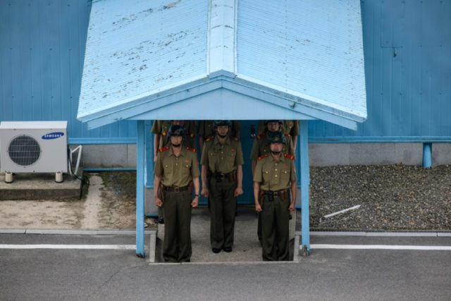 Korean People's Army soldiers stand beneath the entrance to a pavillion before the Military Demarcation Line at the truce village of Panmunjom on the North Korean side of the Demilitarized Zone separating North and South Korea