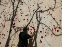 A member of the Kurdistan Democratic Party of Iran (KDPI) sprays red paint at holes in a wall created by shrapnel in the wake of a rocket attack at the party's headquarters in Koysinjaq, in Iraqi Kurdistan, September 12, 2018