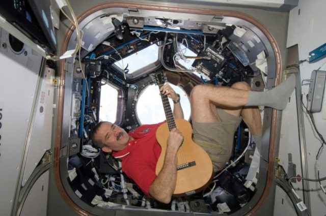 """Canadian astronaut Chris Hadfield -- made famous for his rendition of the David Bowie song """"Space Oddity"""" while aboard the International Space Station -- strums his guitar on the ISS in this 2012 NASA photo"""