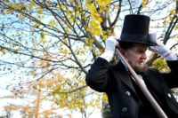 A man portraying US President Abraham Lincoln wears an example of Lincoln's trademark stovepipe hat