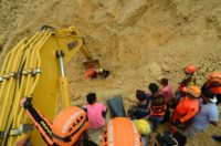 Dozens were missing as rescuers searched the site of a monsoon landslide in the central Philippines