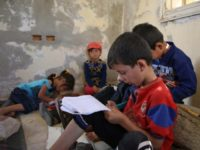 In abandoned villa, Syrian children study on the ground