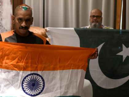 """Sudhir Kumar (left) and Mohammad Basheer display their rival India and Pakistan flags in Dubai for the Asian Cup. """"Friendship has no boundaries"""" says Kumar"""