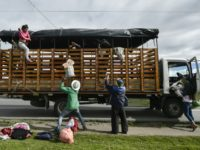 A Venezuelan migrant family get off a truck on the Pan-American highway, between Pasto and Ipiales in Colombia, on August 23, 2018.